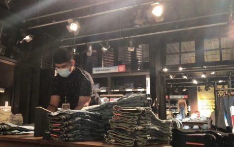 Jon De Leon  refolds and restocks the jeans showcased on the sales floor at Hollister Pearlridge.