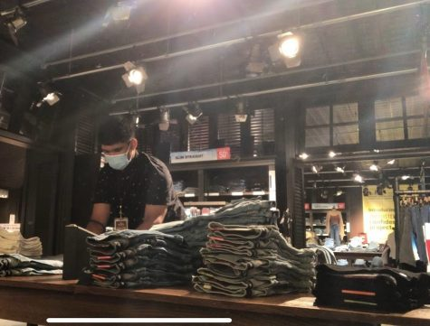 Jon De Leon  refolds and restocks the jeans showcased on the sales floor at Hollister Pearlridge.
